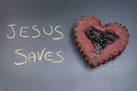 In the picture a rosary iron placed over a heart of red wax, on the left side the inscription Jesus Saves made with a crayon.