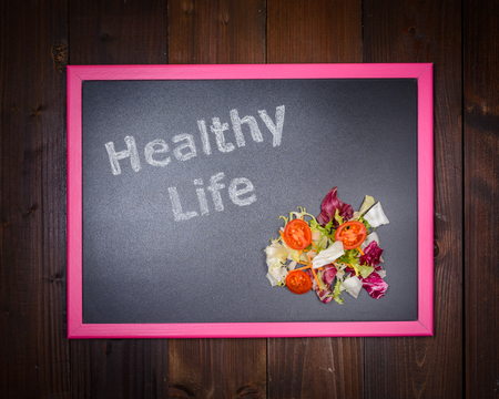 side salad: In the picture a blackboard, on the left side with written Healthy Life and on the right side salad of vegetables on wooden background