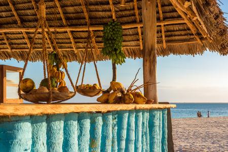 En el bar de la playa de imagen en Nungwi (Zanzíbar) al atardecer, con el coco expuesto, el plátano y la barra de frutas tropicales .Este está hecha con caña de bambú, madera y paja con cuerda.