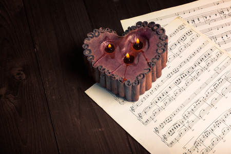 octave: In the picture lit candle with the shape of heart, aged pages of sheet music and wooden background,used split tonig for oldvintage style.