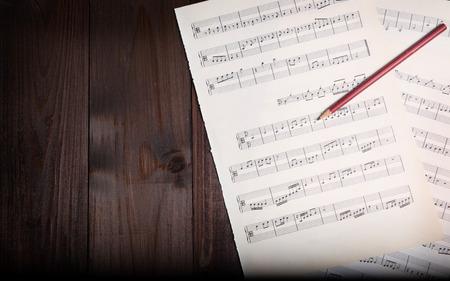 pentagramma musicale: Nelle pagine di immagini in et� di spartiti, matita e sfondo di legno, sopra la vista.