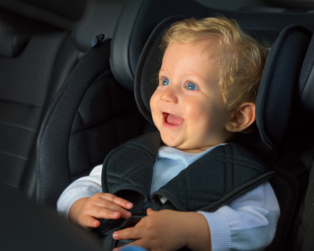 Baby boy 8 months old smiling in a safety car seat. Banco de Imagens