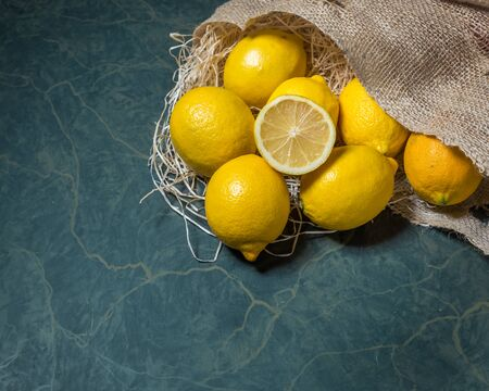 horizontal format: Fresh picked lemons spilling from a burlap sack. Horizontal format with copy space.