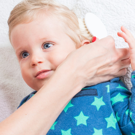Mom combing the baby with blonde hair, while the toddler is lying.