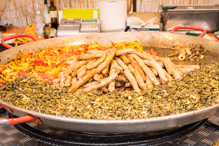 Typical food of Puglia with sausage, turnip top and peppers, prepared in a large pot during a food fair