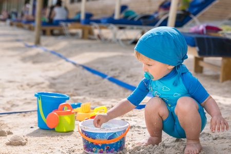 Awesome baby boy plays at the sandy beach during the day
