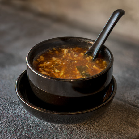 Sour soup on black iron plate on grey stone slate background. side view,close up.