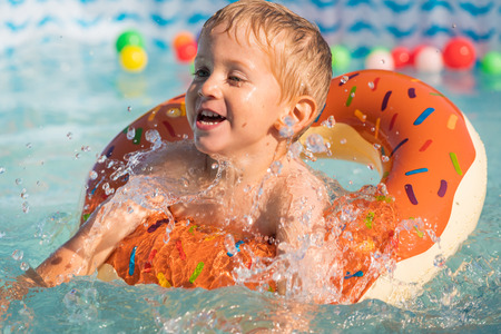 Happy little boy playing with colorful inflatable ring in outdoor swimming pool on hot summer day. Kids learn to swim. Child water toys.close up. Stock fotó