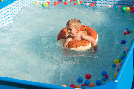 Happy baby boy playing with colorful inflatable ring in outdoor small swimming pool on hot summer day. Kids learn to swim. Child water toys.