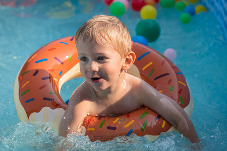 Happy child boy playing with colorful inflatable ring in outdoor swimming pool on hot summer day. Kids learn to swim. Child water toys.