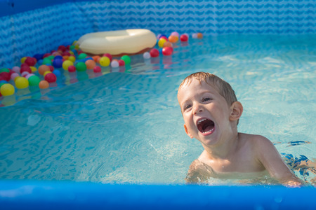 child boy playing in small baby pool.baby swim and splash. Happy little boy playing with water toys on hot summer day. Family having fun outdoors in the backyard.