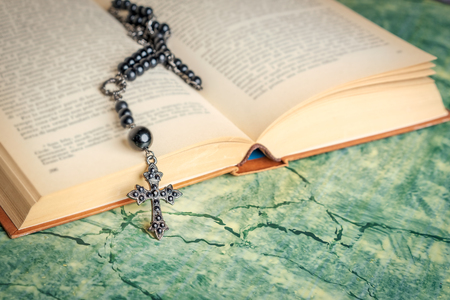 Black rosary and cross on the Bible on a green surface. Religion at school. 写真素材 - 116489927