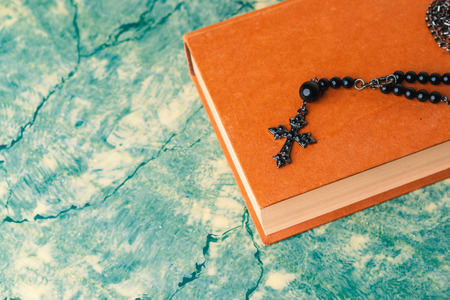 Black rosary and cross resting on the closed book at green table, seen from above.religion school concept.Vintage style. 写真素材 - 116489928