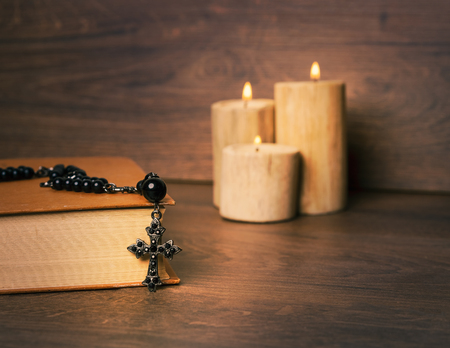 Black rosary and cross on the Bible at wooden table,background candle. Religion at school.vintage style. 写真素材