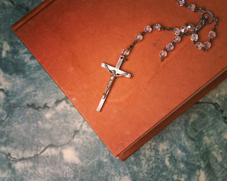 Silver rosary and cross resting on the closed book at green table, seen from above.religion school concept.Vintage style. 写真素材