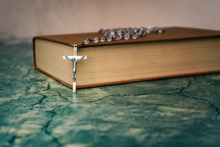 Silver rosary and cross resting on the closed book at green table,front view.religion school concept.Vintage style. 写真素材 - 116489935
