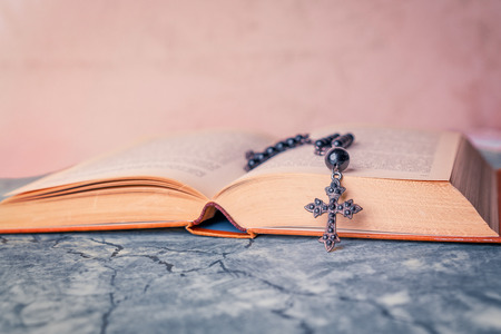 Black rosary and cross on the Bible on a gray table. Religion at school. 写真素材