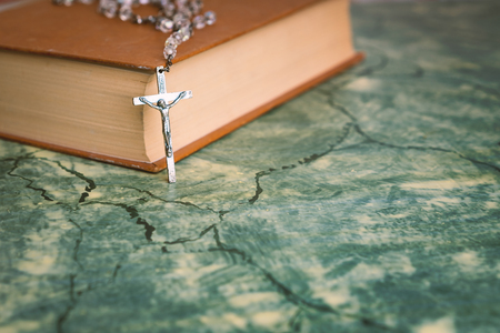 Silver rosary and cross resting on the closed book at green table,front view.religion school concept.Vintage style. 写真素材 - 116489895