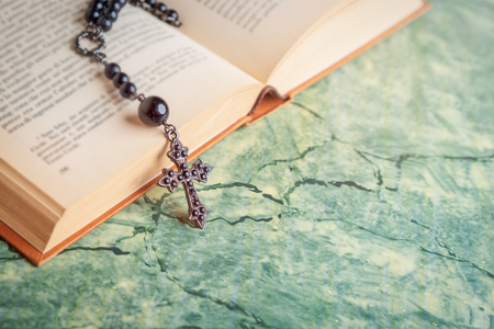 Black rosary and cross on the Bible on a green table. Religion at school.