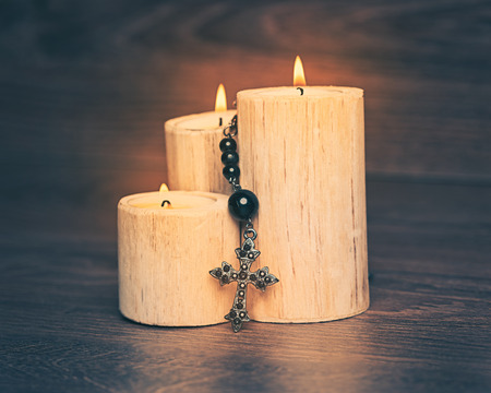 Black rosary on the Candle at wooden table,religion concept,vintage style with split toning. 写真素材