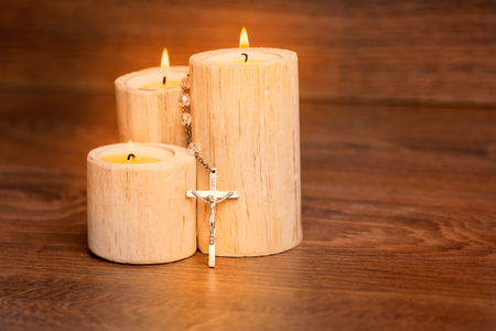 Silver rosary with Jesus on the Candle at wooden table,religion concept,vintage style.