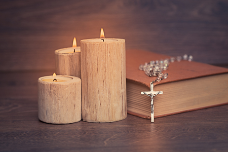 Silver rosary and crucifix resting on closed book near the candles on wooden table, religion school concept. Vintage style. 写真素材