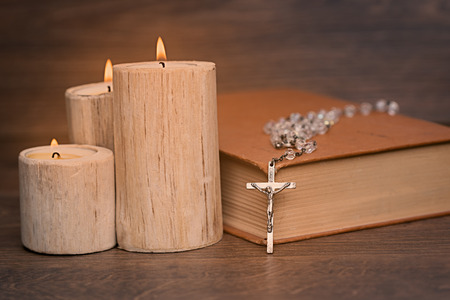 Silver rosary and crucifix resting on closed book near the candles on wooden table, religion school concept. Vintage style. 写真素材 - 116489856