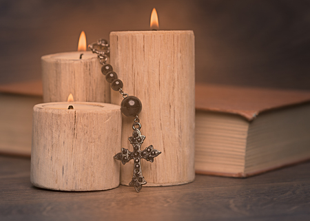 black rosary and crucifix resting on closed book near the candles on wooden table, religion school concept. Vintage style. 写真素材 - 116489861