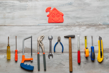 Set of work tool on gray wooden background with icon of house in space, industry engineer tool concept.still-life.