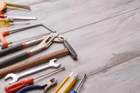 Schraubendreher, Hammer, Maßband und anderes Werkzeug für Bauwerkzeuge auf grauem Holzhintergrund mit Kopierraum, Werkzeugkonzept für Industrieingenieure. Stillleben.
