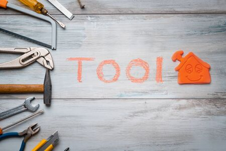 Set of work tool on rustic wooden background with house icon and written tool in space, industry engineer tool concept.