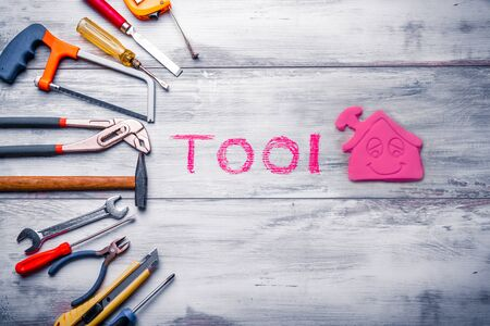 Set of work tool on rustic wooden background with house icon and written tool in space, industry engineer tool concept.still-life.
