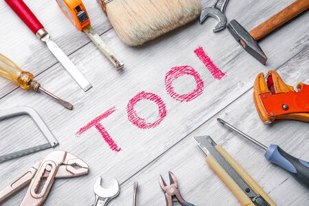 Set of work tools on rustic wooden background with written