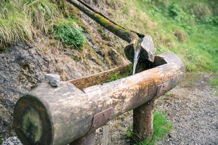 Natural raw unfiltered water flowing from wooden fountain spring at the Val Vertova torrent near Bergamo.Italy
