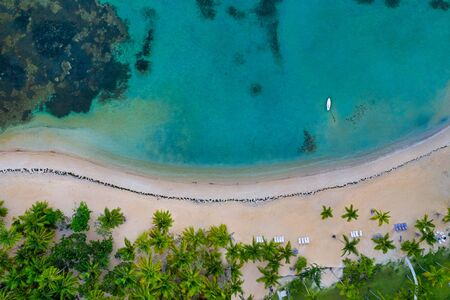Aerial view of tropical beach with white boat anchored.Samana peninsula,El Portillo beach,Dominican Republic.