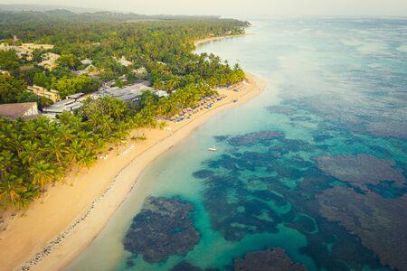 Drone shot of tropical beach with white boat anchored.Samana peninsula,Bahia Principe beach,Dominican Republic.