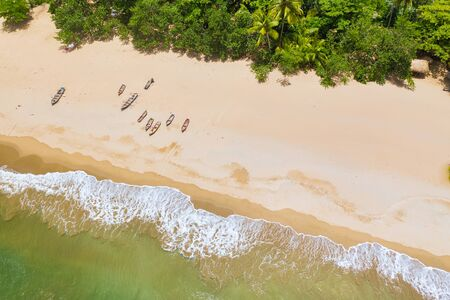 Aerial view of boats moored on the beach, Caribbean beach with waves. Фото со стока - 132050795