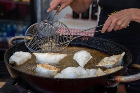Dumplings fried,Deep Frying in hot oil pan, street food during the day,italian traditional food.