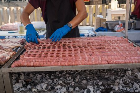 BBQ Sausage lined up on a large outdoor grill with smoke coming up from the fire below. person in black apron blue shirt gloved hand holding tongs turning meat Banco de Imagens