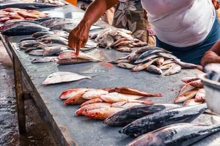 retail sale of fish on the dirty counter at the fish market, around people who watch and choose fish.
