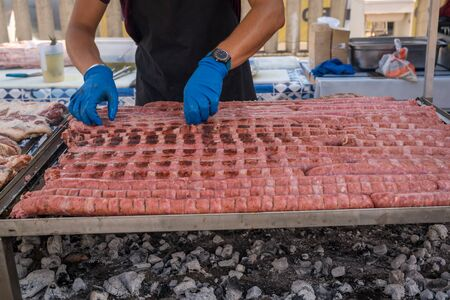 BBQ Sausage lined up on a large outdoor grill with smoke coming up from the fire below. person in black apron blue shirt gloved hand holding tongs turning meat Фото со стока