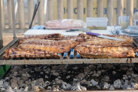 BBQ rack of pork ribs lined up on a large outdoor grill with smoke coming up from the fire below.
