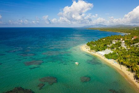 Aerial view of tropical beach with white boat anchored.Samana peninsula,Bahia Principe beach,Dominican Republic.