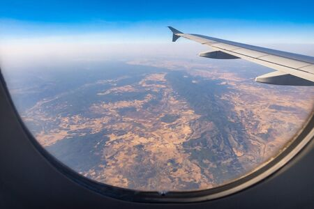 Looking through aircraft window during flight. Aircraft wing over blue skies and pyrenees mountains.Copy space. Фото со стока - 133077506