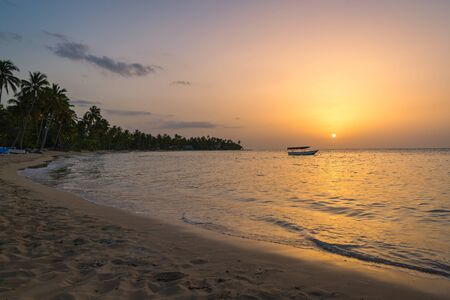 Landscape of paradise tropical island beach with boat background, sunset shot at Dominican republic ,Grand Bahia principe beach. Фото со стока