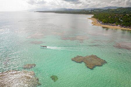 Aerial photography of tropical beach and boat while sailing .Samana peninsula,Bahia Principe beach,Dominican Republic. Фото со стока