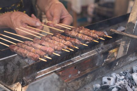 Man cooking marinated meat, Pork meat grilling on wooden skewer, outdoor grill with smoke coming up from the fire below. close up