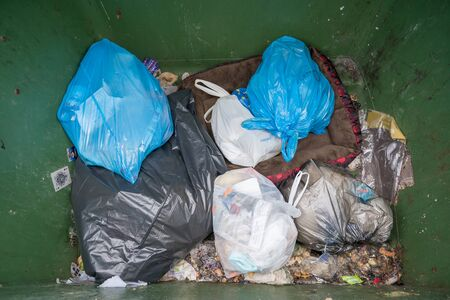 Milan, Italy - December 02, 2019: selective waste collection bins, big green dumpster full of garbage bags,Undifferentiated waste collection