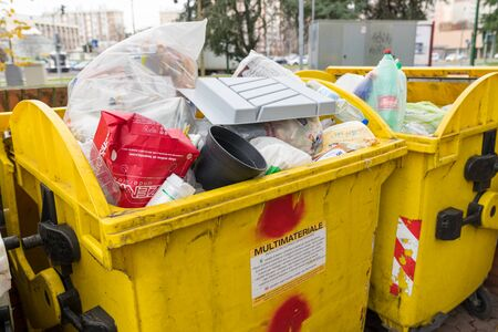 Milan, Italy - December 02, 2019: selective waste collection bins, big yellow dumpster full of garbage bags,Undifferentiated waste collection Фото со стока