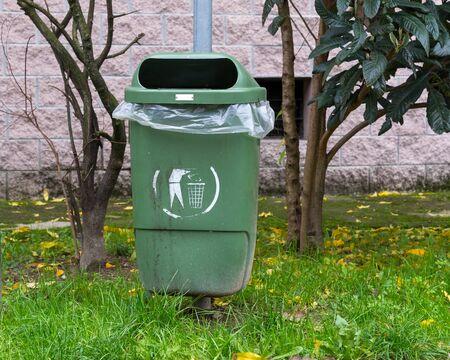 A little green dumpster of garbage empty